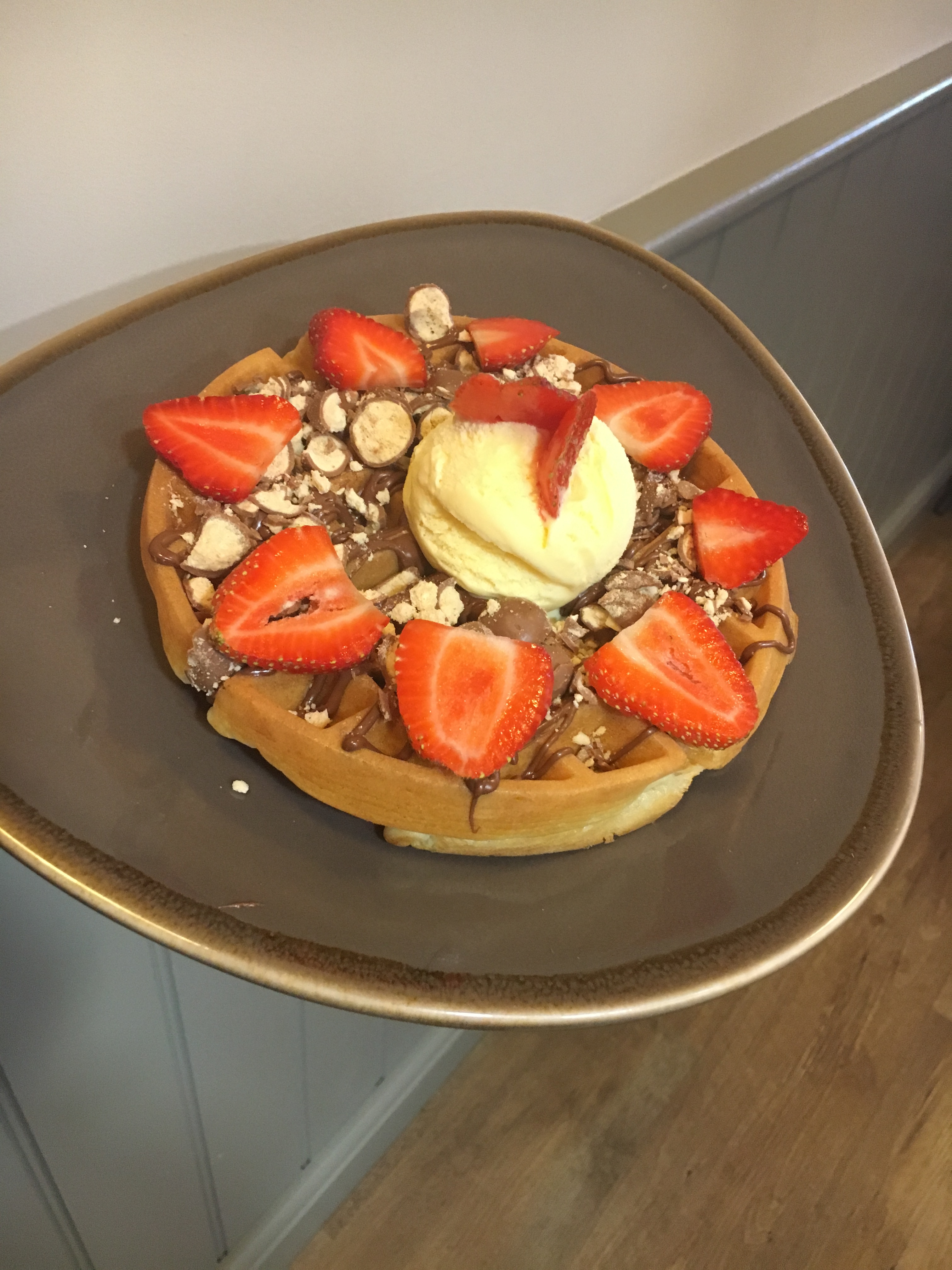 Waffle-topped-with-vanilla-ice-cream-strawberries-nutella-crushed-maltezers